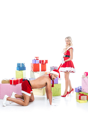 seductive young woman in christmas dress using her boyfriend scarf as leash in front of pile of gift boxes isolated on white background Stock Photo