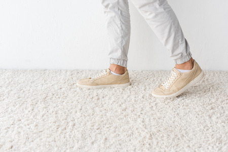 cropped view of male legs on carpet against white wall