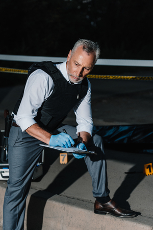 serious middle aged policeman writing in clipboard at crime scene with corpse in body bag Stock Photo