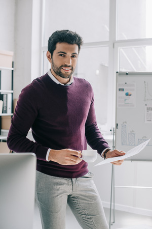 handsome businessman in burgundy sweater holding cup of coffee and documents in office
