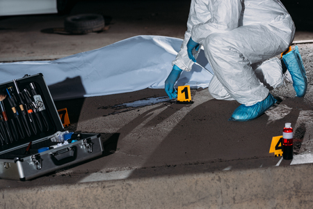 cropped image of criminologist in protective suit and latex gloves collecting evidence at crime scene with corpse Stock Photo