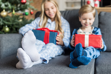 adorable happy kids in pajamas holding gift boxes at christmas time