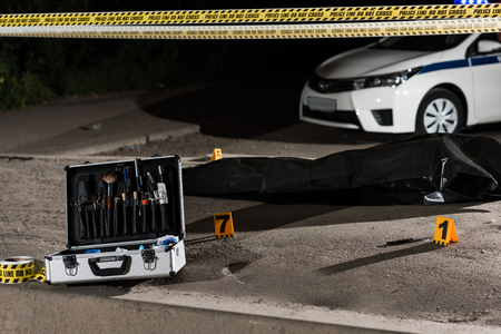 case with investigation tools, car, police line and corpse in body bag at crime scene Zdjęcie Seryjne - 111854372