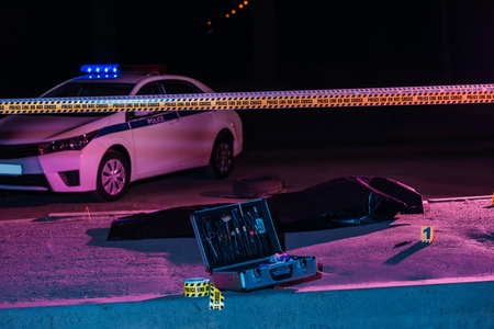 toned picture of crime scene with police car, case with investigation tools, cross line and corpse in body bag Stock Photo