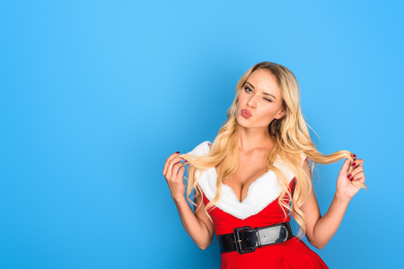 sexy young woman in christmas dress winking isolated on blue background