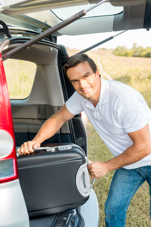 handsome man packing suitcase into luggage boot of car in field and looking at camera