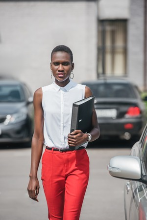 stylish attractive african american businesswoman walking near car on parking