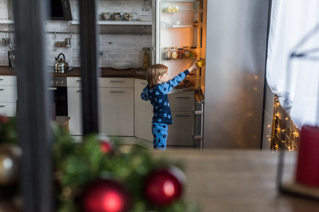 selective focus of little boy on pajamas opening refrigerator