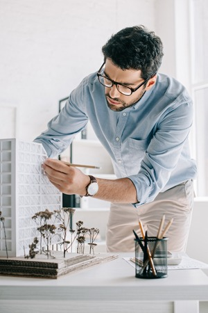 handsome architect working with architecture model on table in office Standard-Bild