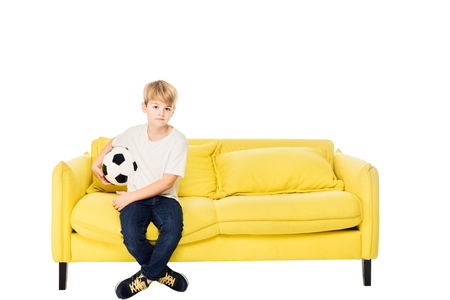 adorable boy sitting with football ball on yellow sofa isolated on white and looking at camera Imagens