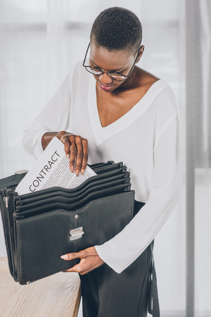 stylish attractive african american businesswoman putting contract into briefcase in office 스톡 콘텐츠