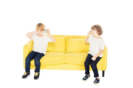 adorable boys playing with tin cans phone on yellow sofa isolated on white
