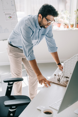 handsome architect leaning on table and looking at architecture model in office