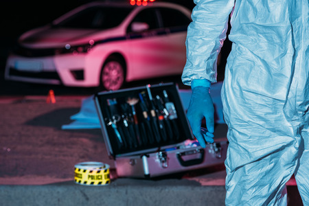 cropped image of male male criminologist in protective suit standing near case with investigation tools at crime scene