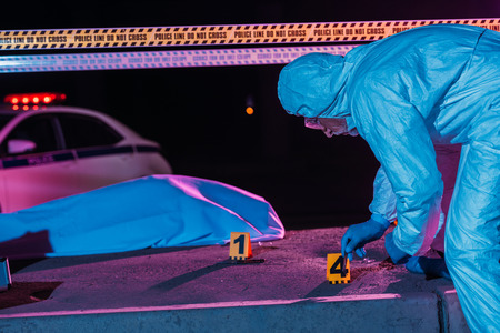 middle aged male criminologist in protective suit and latex gloves collecting evidence at crime scene with corpse Stock Photo