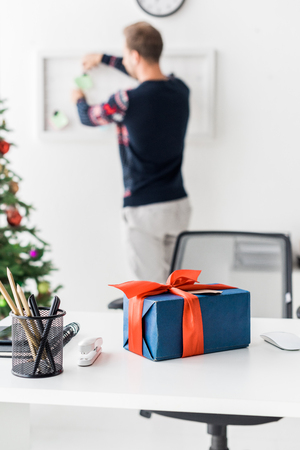 christmas gift box on table and businessman working on background