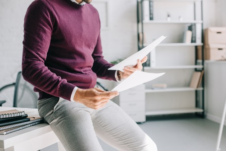 cropped image of businessman in burgundy sweater leaning on table and holding documents in office