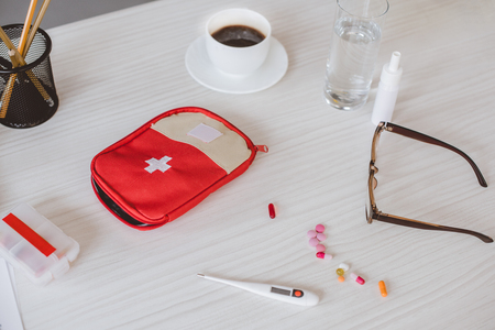 first aid kit, cup of coffee and pills on table in office Stock Photo
