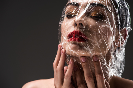 sensual young woman with face wrapped in wet transparent cellophane isolated on black Stock Photo