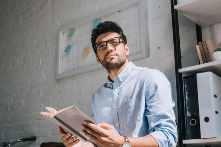 handsome architect in glasses holding book and looking away in office