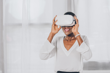 smiling stylish african american businesswoman in virtual reality headset in office