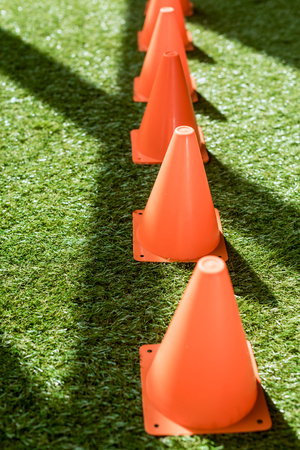 row of safety cones standing on green grass Stockfoto