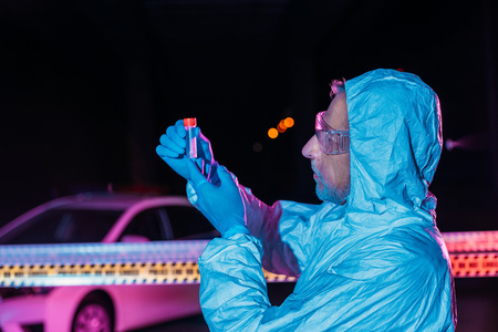 side view of middle aged male criminologist in protective suit and latex gloves collecting evidence at crime scene with corpse