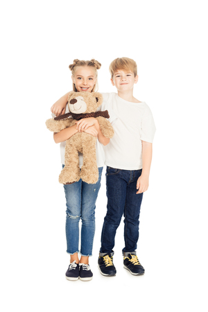 smiling kids hugging, holding teddy bear and looking at camera isolated on white Stock Photo