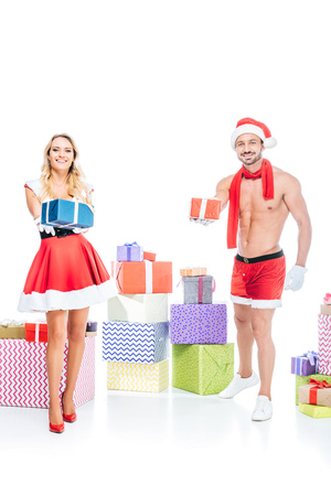 attractive young woman in santa dress and muscular shirtless man in christmas hat giving presents isolated on white background Stock Photo