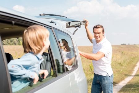 little son looking at father out window while he opening car trunk in field