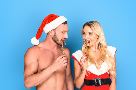 happy boyfriend in christmas hat and girlfriend santa dress licking striped christmas sticks isolated on blue background