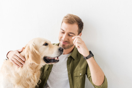 man stroking golden retriever dog against white wall Фото со стока