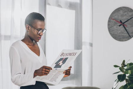 side view of stylish attractive african american businesswoman reading newspaper in office
