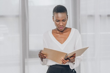 stylish attractive african american businesswoman reading documents in office