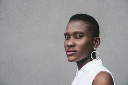 stylish attractive african american woman looking at camera near grey wall
