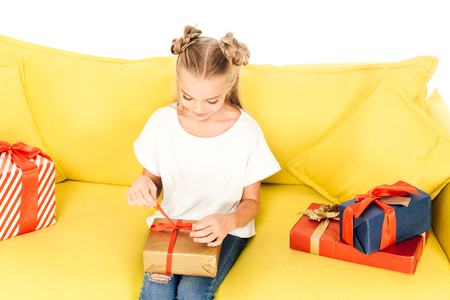 high angle view of adorable child opening present on yellow sofa isolated on white Stock Photo
