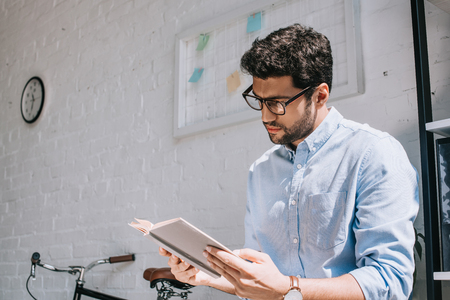 handsome architect in glasses reading book in office