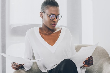 stylish attractive african american businesswoman sitting in armchair and reading documents in office