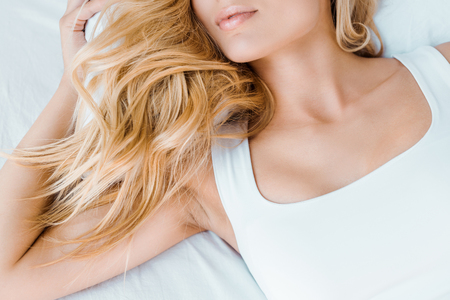 cropped shot of young blonde woman lying in bed 版權商用圖片