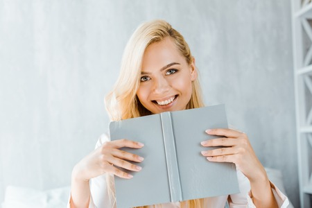 happy young woman holding book and smiling at camera in bedroom