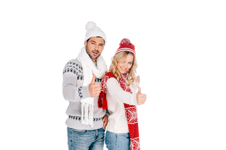 beautiful young couple in winter outfit showing thumbs up and smiling at camera isolated on white