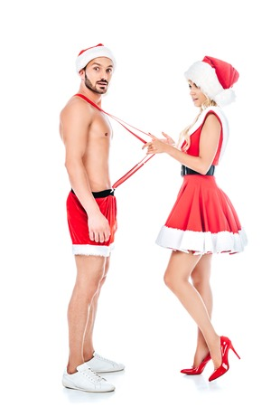 side view of young woman in santa hat and dress pulling suspenders of her shocked boyfriend isolated on white background 写真素材