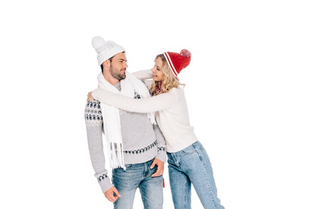 beautiful happy young couple in sweaters and hats hugging and smiling each other isolated on white
