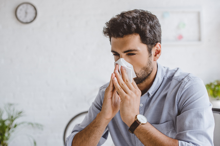 sick manager blowing nose in tissue in office