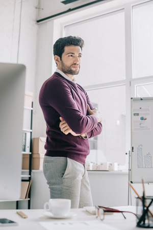 handsome designer in burgundy sweater standing with crossed arms and looking away in office Foto de archivo