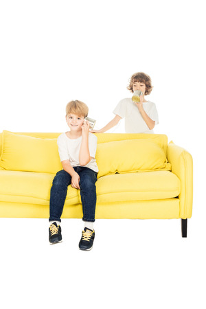 cheerful boys playing with tin cans phone on yellow sofa isolated on white Stock Photo