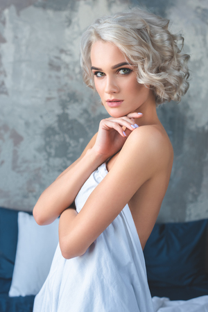 attractive naked young woman covering her body with white cloth and looking at camera