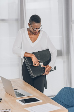 stylish attractive african american businesswoman locking briefcase in office