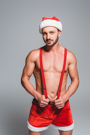 confident sexy man in christmas hat and shorts holding suspenders isolated on grey background Stock Photo