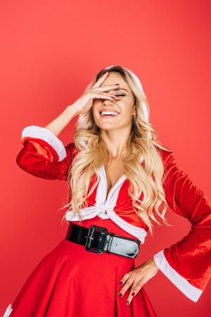laughing santa girl in christmas dress gesturing by hand isolated on red background Stok Fotoğraf